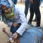 Razan al-Najjar, the 21 year old Gaza medic killed by an Israeli sniper on June 1, treating an injured man, undated photo from Palestine Live on Twitter.