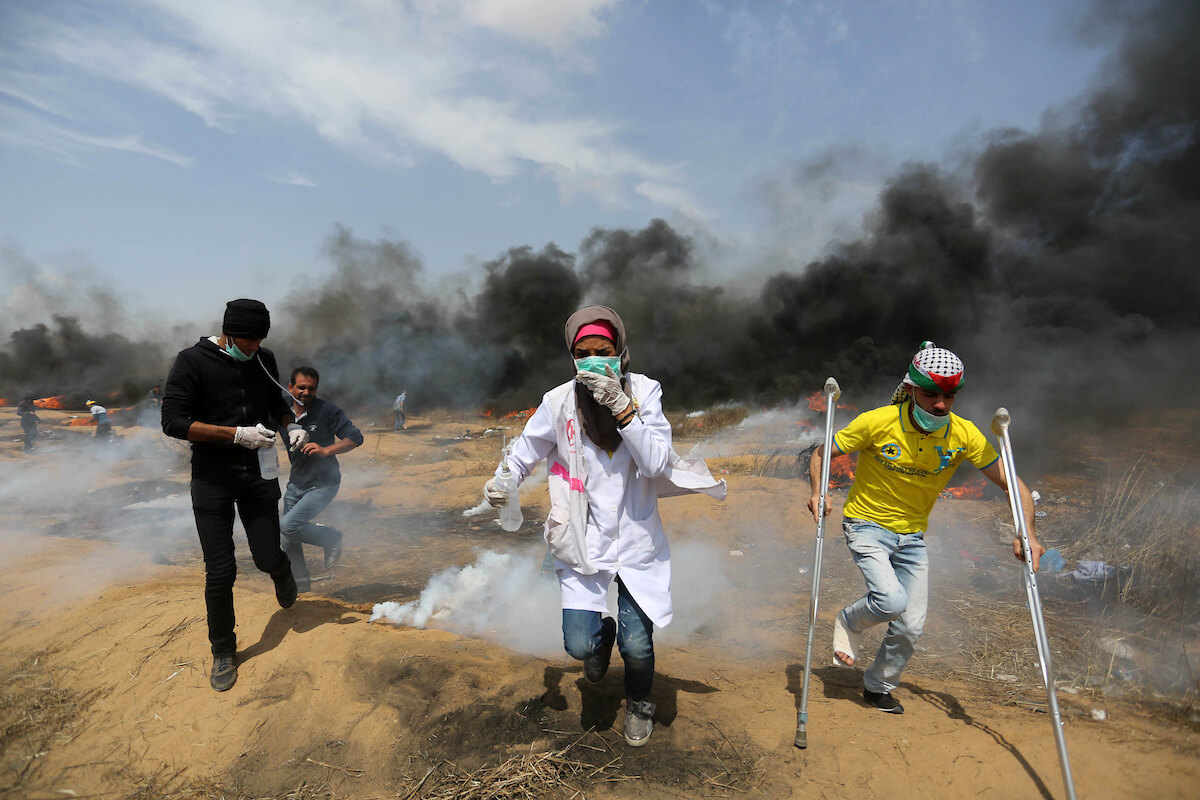 "A file photo taken on April 27, 2018 shows Palestinian protesters clash with Israeli security forces during tents protest demanding the right to return to their homeland, at the Israel-Gaza border, in Khan Younis in the southern Gaza Strip. Israel rejected the findings of a UN probe released on February 28 into its soldiers' response to Gaza unrest that began in March last year, calling it ""hostile, deceitful and biased."" (Photo: Ashraf Amra/APA Images)"