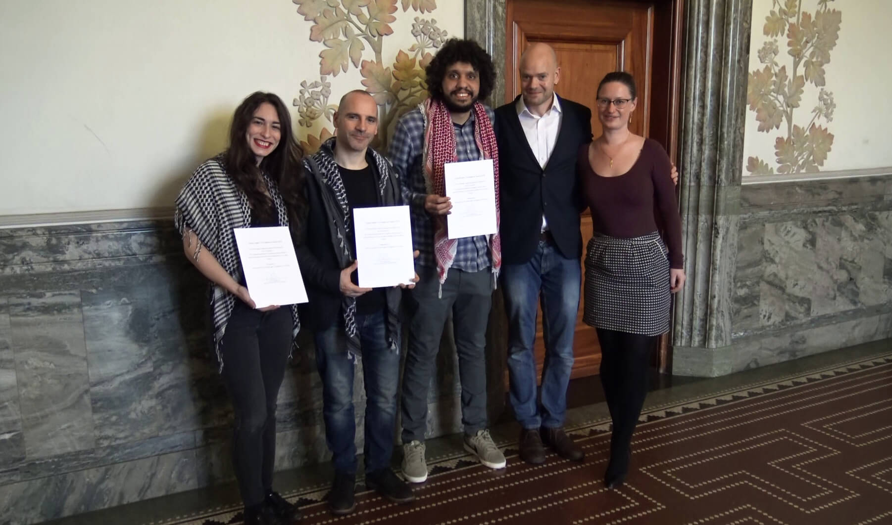 The Humboldt 3, Stavit Sinai, Ronnie Barkan, and Majed Abusalama, receive an award from Copenhagen's Mayor for Technical and Environmental Affairs