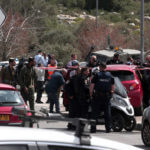 Members of the Israeli Israeli security forces stand guard next to a car at the site of an attack at the Ariel junction