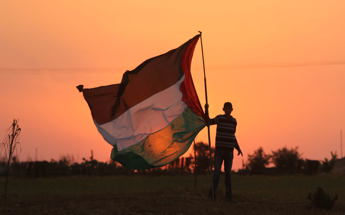 A Palestinian man waves a Palestine flag ahead of the beginning of the Great March of Return protests on March 29, 2018. (Photo: Ashraf Amra/ APA Images)