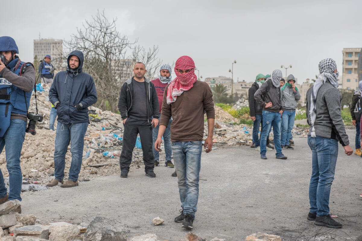Palestinian protesters gather to throw stones at the northern entrance of Al Bireh, close to the settlement of Beit El. This location is close to a checkpoint, an army base and a refugee camp. It frequently witnesses clashes between the Israeli army and Palestinians. (Photo: Annelies Keuleers)