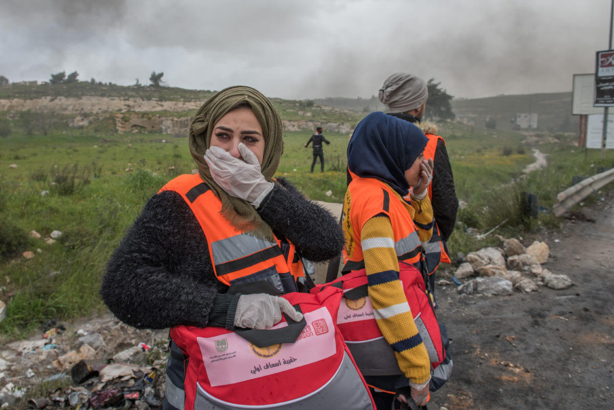 A Palestinian medic uses her hand to cover her nose as the stench of skunk pervades the air