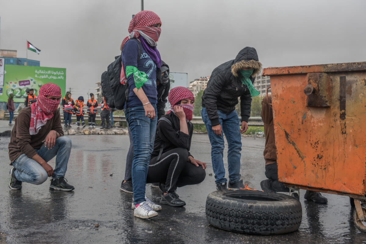 Palestinian protesters use a waste container to take cover from the Israeli army