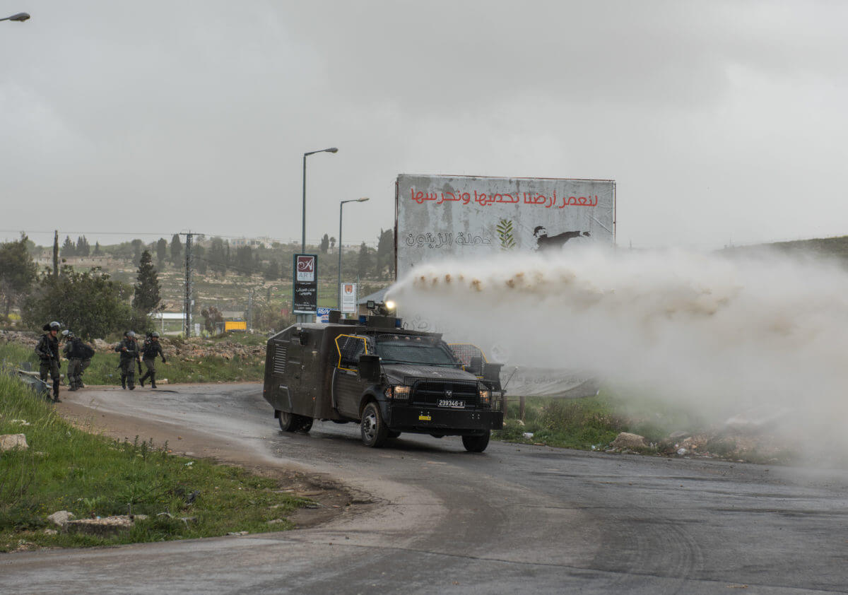 An Israeli army jeep sprays skunk water towards protesters