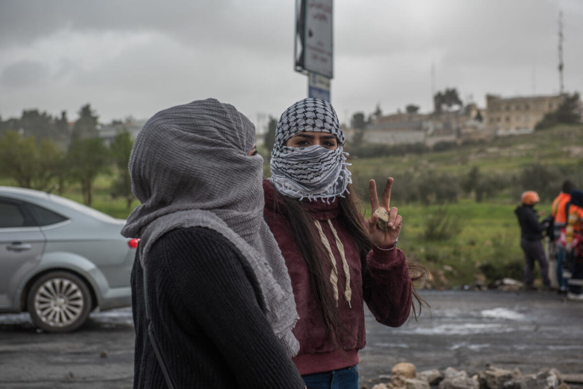 A female Palestinian protester makes a victory sign.