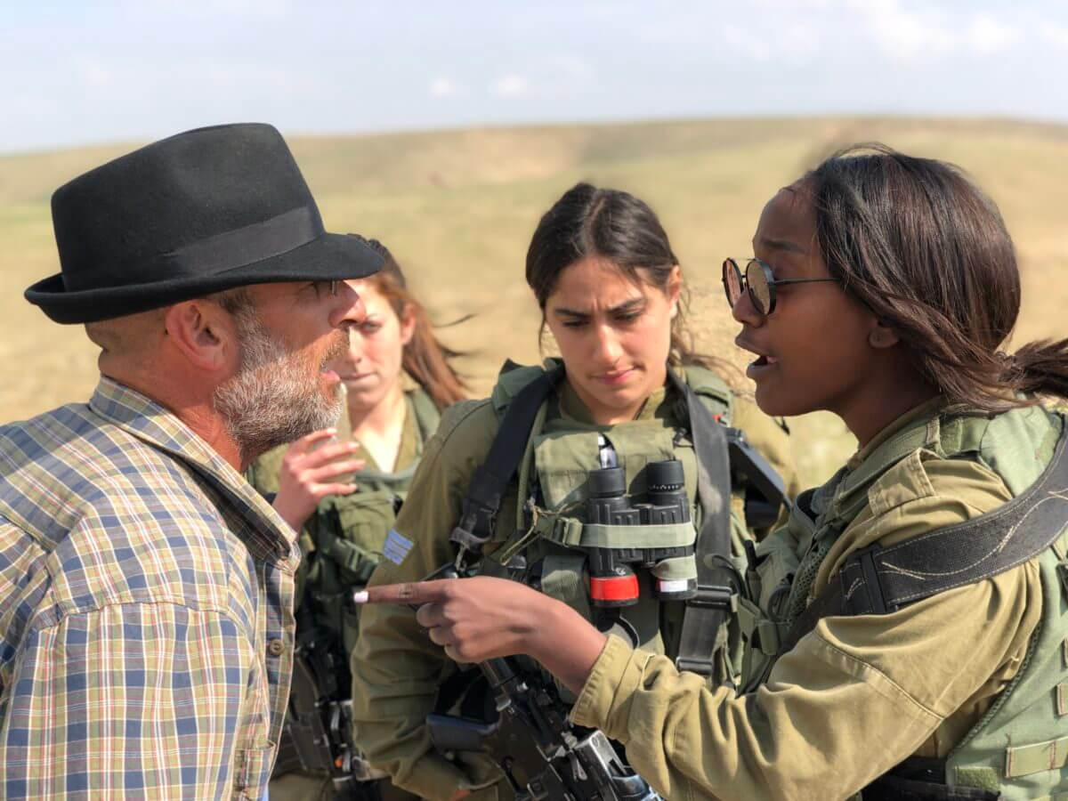 Israeli activist Guy Hirschfeld argues with Israeli soldiers. He explains that they're doing the work of the settlers by kicking Palestinian shepherds off their land. (Photo: Antony Loewenstein)