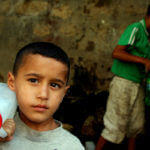 Palestinian boys fill bottles of water in the West Bank village of Qarawah Bani Zeid