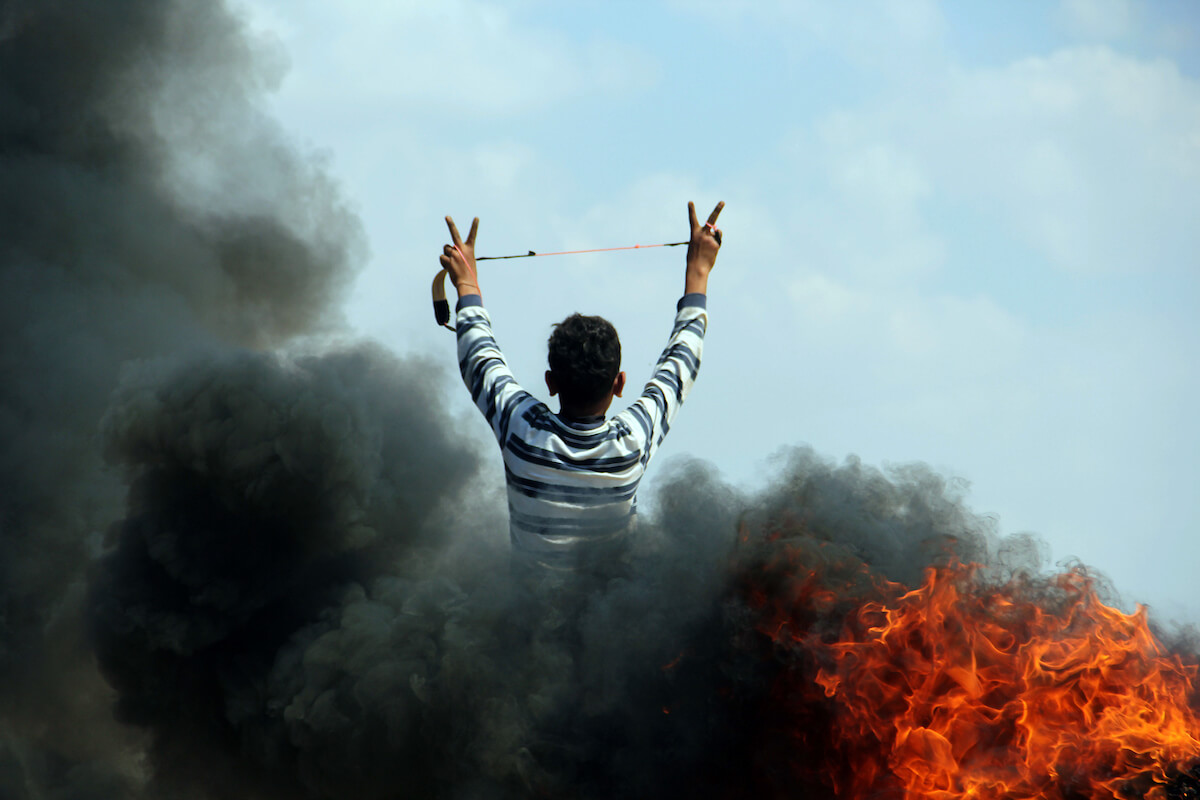 A Palestinian youth flashes the victory sign during clashes with Israeli security forces near the border with Israel, east of Jabalia refugee camp in northern Gaza Strip, May 21, 2014. (Photo: Khaled al-Sabbah/APA Images)