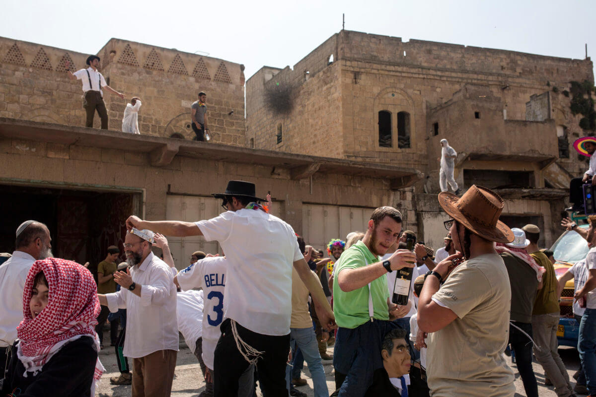 Israeli settlers dance on top of Palestinian homes