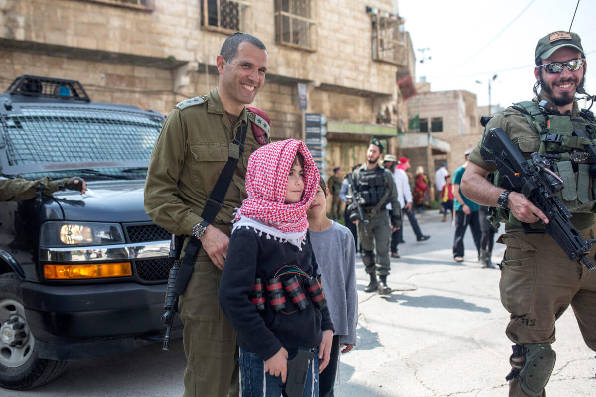 An Israeli child dressed with a keffiyeh and fake suicide bomb belt participates in the settler Purim march