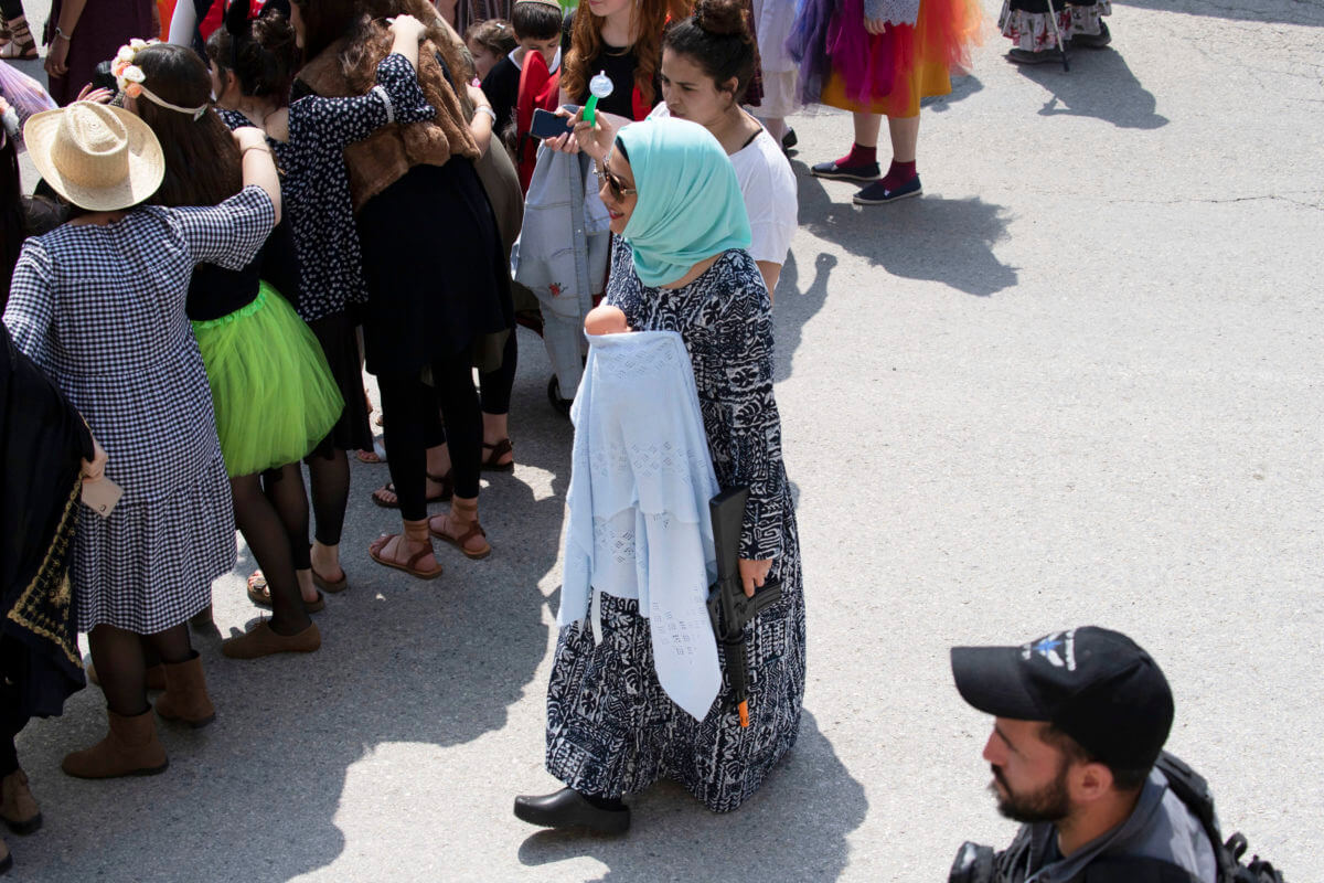 """A Israeli woman dressed as an """"Arab"""" wearing a fake baby and a weapon marching in the settler Purim march in the H2 area of the West Bank city of Hebron"""