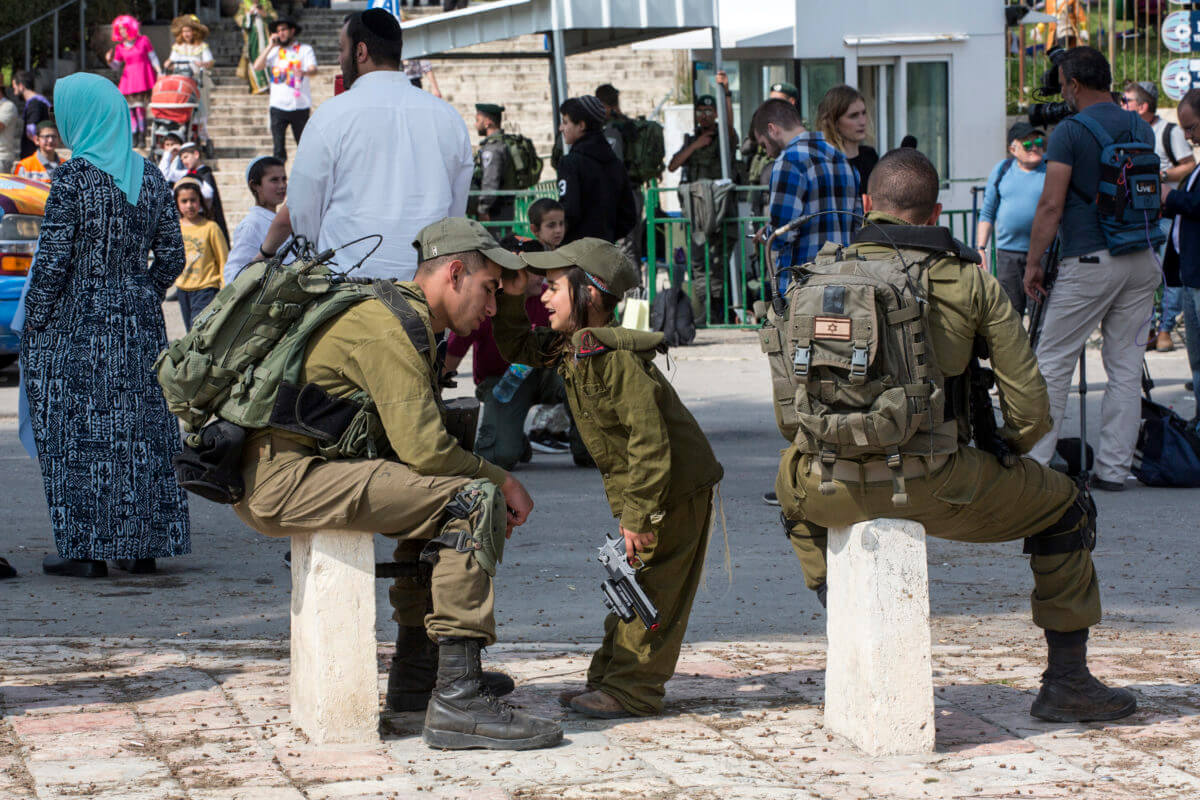 An Israeli child dressed up as a soldier participates to the settler Purim march in the H2 area of the West Bank city of Hebron, March 21, 2019. (Photo: Activestills.org)