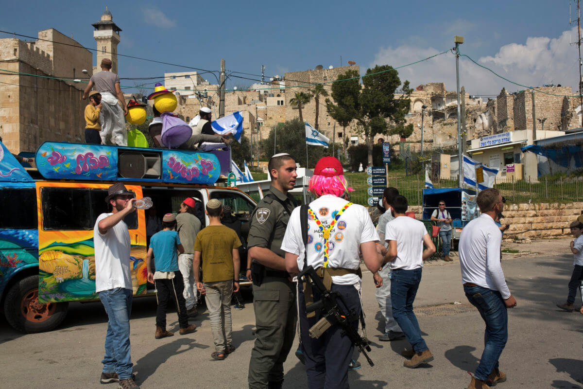 armed Israeli settler participates in the Purim march