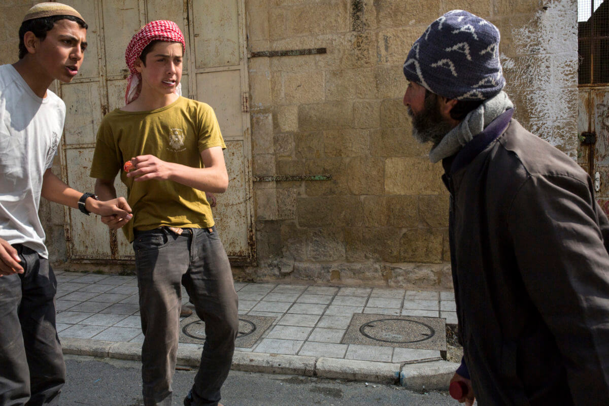 Two Israeli settlers harass a Palestinian man during a Purim parade in the H2 area of the West Bank city of Hebron, March 21, 2019. (Photo: Activestills.org)