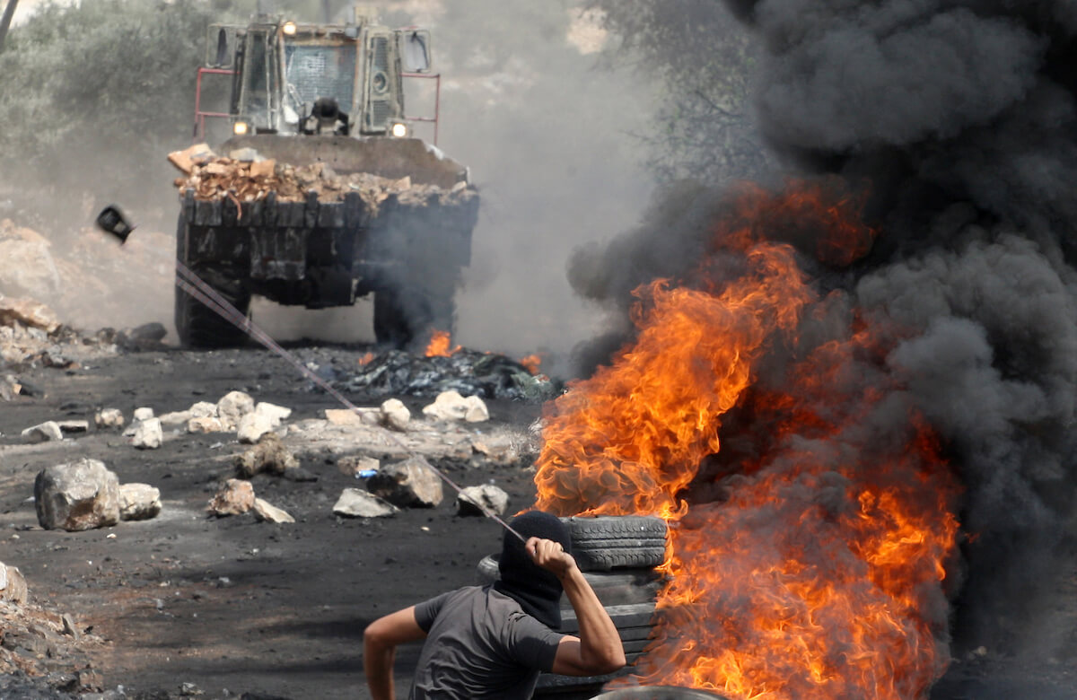 A Palestinian protester uses a slingshot to throw stones towards an Israeli military truck