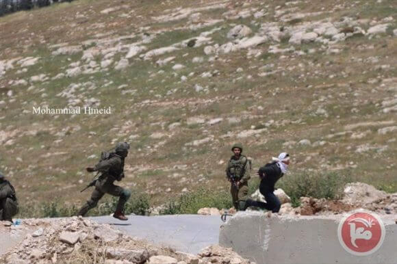 Photo of Israeli forces the teen running away from soldiers moments before he is shot to the ground.