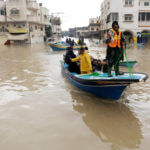 Palestinian civil defense volunteers help people to travel across flood waters in Gaza City following rain storms, on December 14, 2013. A fierce winter storm shut down much of the Middle East at that time, burying Jerusalem in snow, and flooding parts of Gaza. (Photo: Ashraf Amra/APA Images)