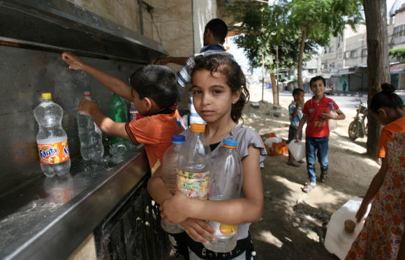 Palestinian children fill bottles with water from a public tap in Rafah in the southern Gaza Strip, July 1, 2014. Israel had bombed the main water line for al-Shati refugee camp and a sewage plant west of Gaza City. (Photo: Eyad Al Baba/APA Images)