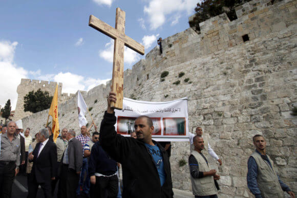 A Palestinian protester holds a cross during a demonstration against acts of vandalism on Christian sites including smashing headstones in a Christian cemetery in Israel and the occupied West Bank, outside Jerusalem's Old City October 6, 2013. (Photo: Saeed Qaq/APA Images)
