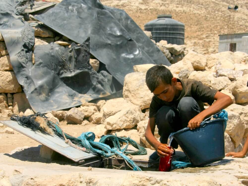 Palestinian draws water from cistern in the village of Khirbet Jenbah
