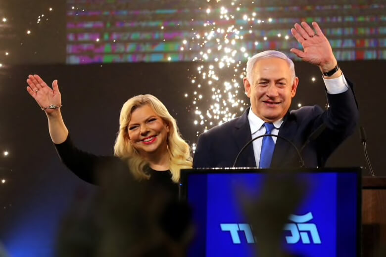 Benjamin Netanyahu and his wife Sara wave as Netanyahu speaks following the announcement of exit polls in Israel's parliamentary election at the party headquarters in Tel Aviv.