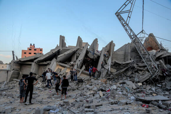 Palestinians inspect the remains of a building following an Israeli airstrike, in Gaza city on May 5, 2019. Israeli warplanes hit the building on Saturday where Anadolu Agency's office is located.