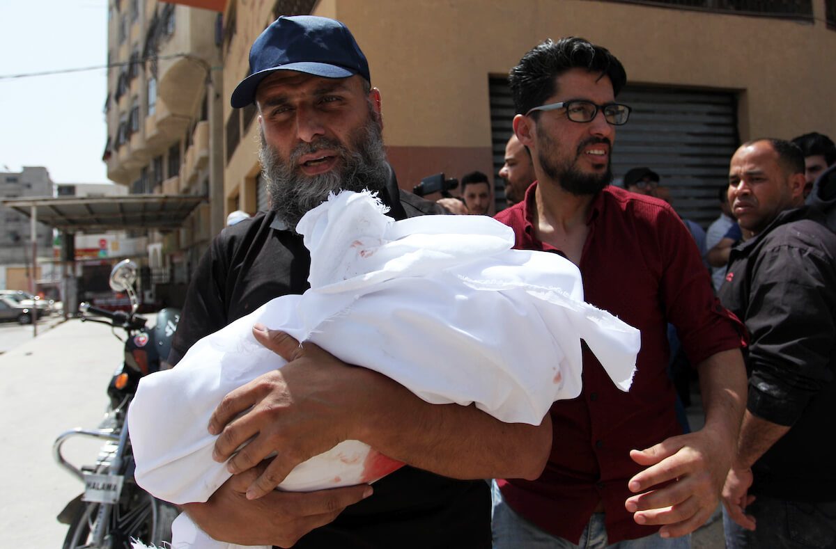 A Palestinian relative carries the body of Maria al-Ghazali, a 4-month old Palestinian killed by an Israeli airstrike on Gaza City on May 6, 2019. (Photo: Mahmoud Ajjour/APA Images)