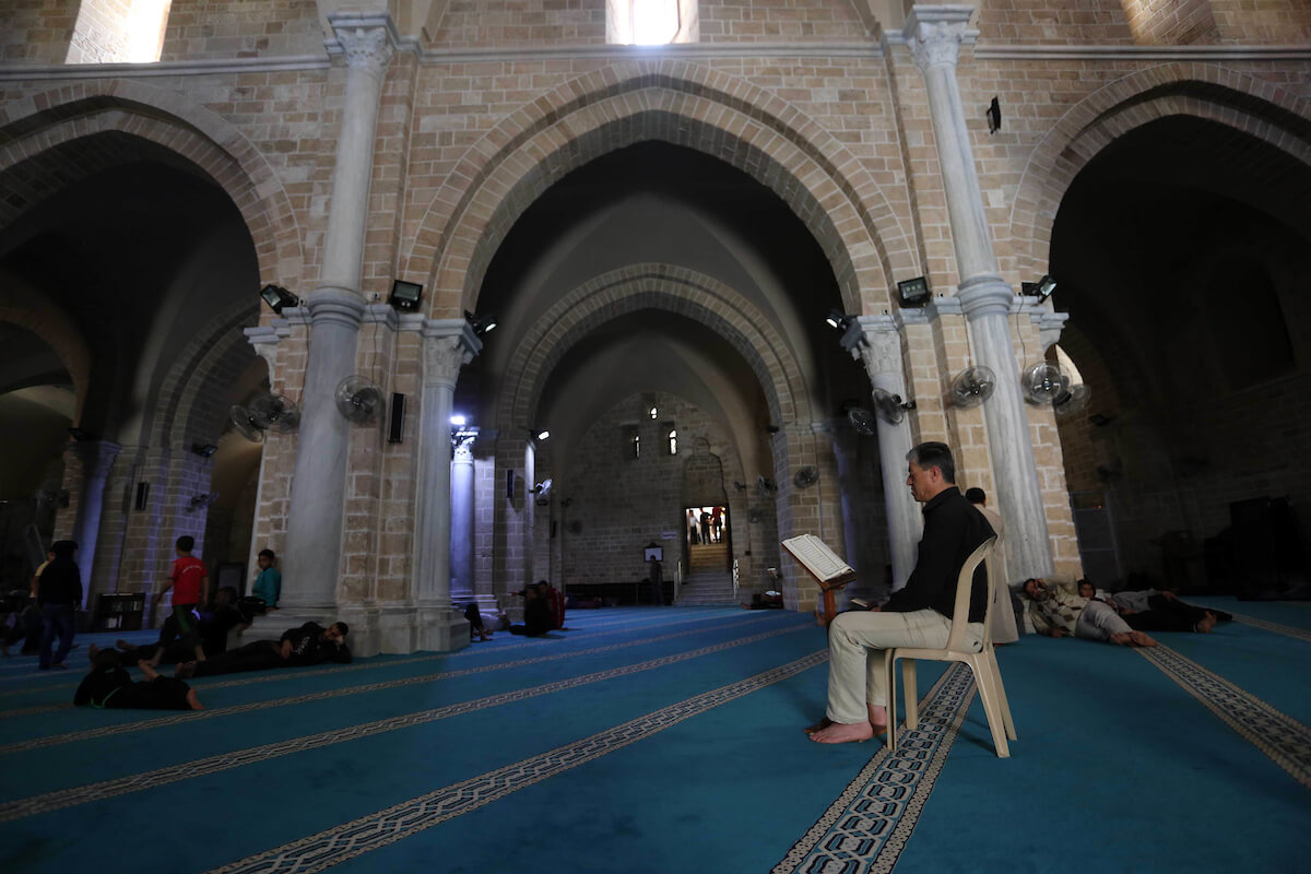 Palestinian reads verses from the Koran at al-Omari mosque, during the Islamic holy month of Ramadan, in Gaza city on 07 May 2019. Muslims around the world celebrate the holy month of Ramadan by praying during the night time and abstaining from eating, drinking, and sexual acts during the period between sunrise and sunset. Photo by Ashraf Amra