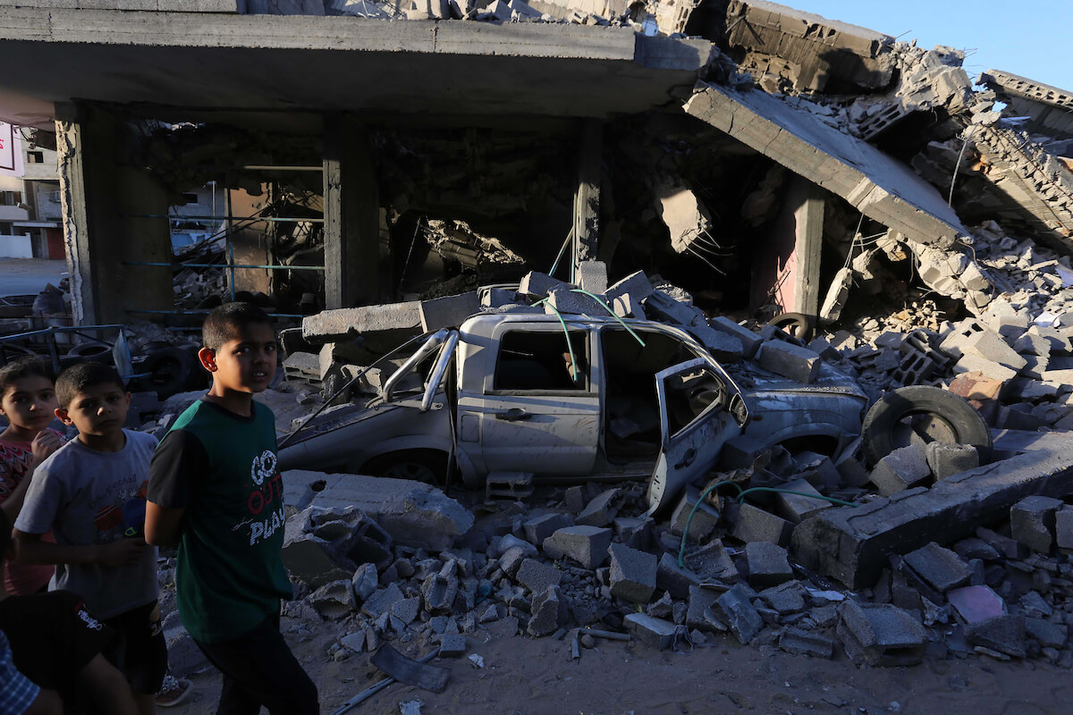 Palestinians walk past the rubble of a building that was destroyed by Israeli air strikes, in Gaza city on May 7, 2019. About 130 residential apartments were completely destroyed, while 700 others were partially destroyed in the three day Israeli strikes on Gaza, Housing Ministery reported. Photo by Ashraf Amra