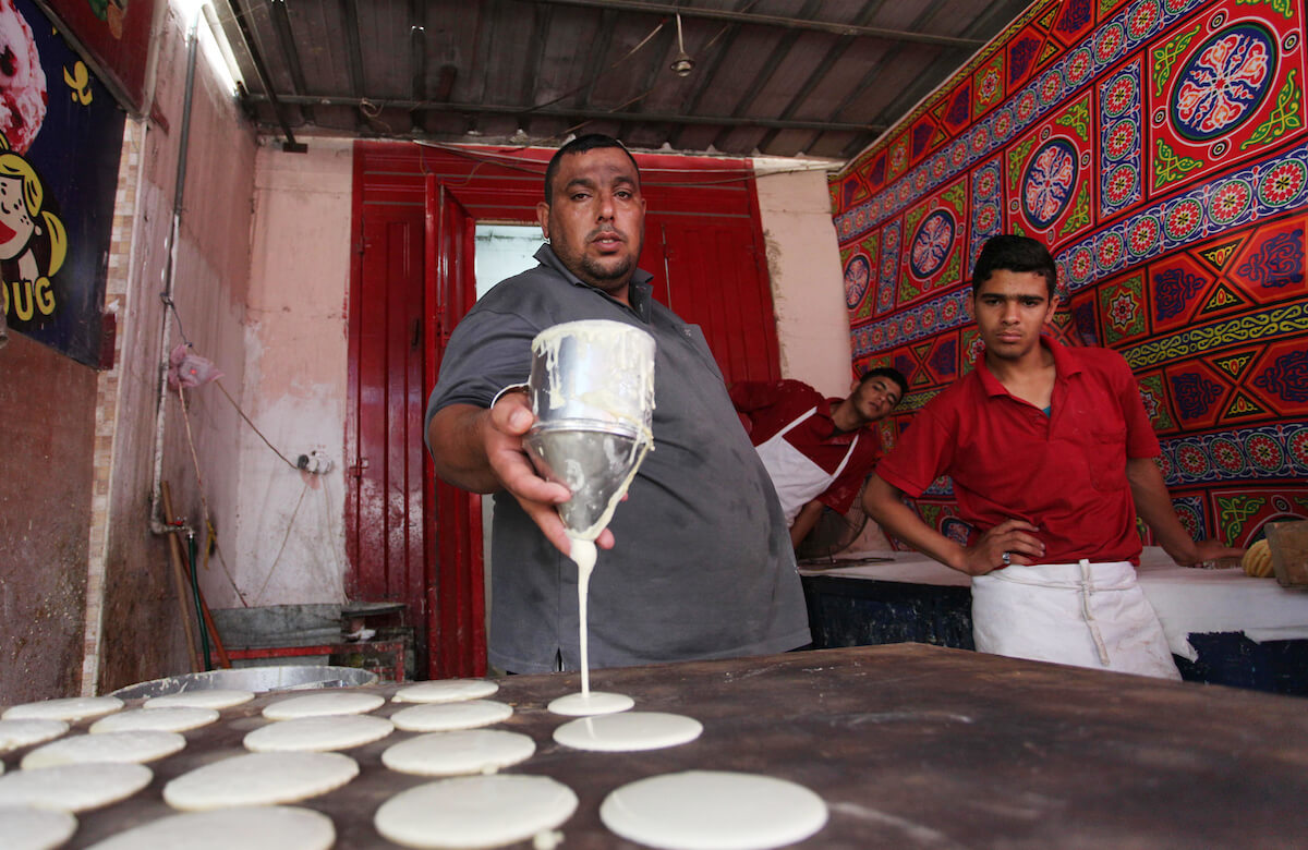 A Palestinian vendor prepares qatayef, traditional pancakes that are popular during the Muslim fasting month of Ramadan, at a market in Gaza City on May 19, 2018. (Photo: Mahmoud Ajour/APA Images)