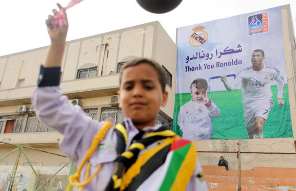 "Poster of Real Madrid footballer Cristiano Ronaldo and Palestinian Ahmed Dawabsha, 5, who met in Spain in 2016 one year after Dawabsha survived an arson attack on his West Bank home in Duma, in which both of his parents and infant brother were killed by Israeli extremists. The poster reads in Arabic, ""Thanks Madrid .. Thanks Ronaldo,"" Yarmouk Stadium, Gaza City, March 27, 2016. (Photo: Ashraf Amra)"
