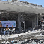 Children watch the concert in the ruins of the al-Qamar building (Photo: Mohammed Asad)