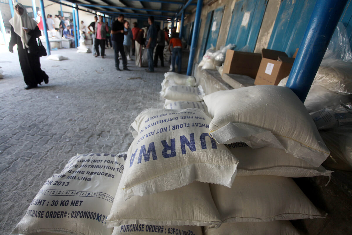 Palestinians receive food aid from UNRWA at a warehouse in al-Shati refugee camp in Gaza City, Sept. 10, 2013. (Photo: Ashraf Amra/APA Images)