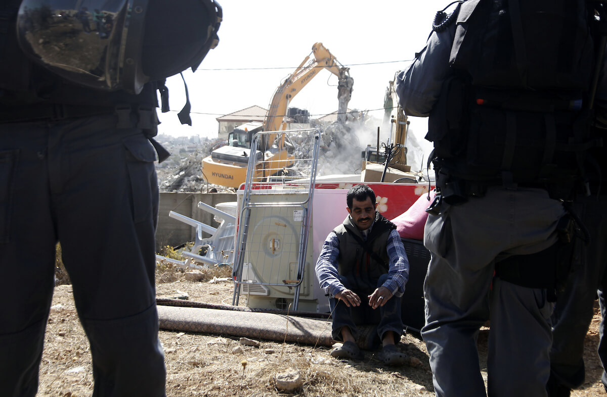 A Palestinian man sits next to belongings removed from his house as Israeli police officers stand guard during a demolition of the house in the East Jerusalem neighborhood of Beit Hanina, October 29, 2013. A statement from the Jerusalem Municipality said there was a court order for the demolition of the house, which was built without a permit. (Photo: Saeed Qaq/APA Images)