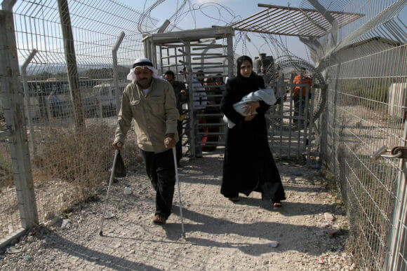 Palestinians cross the Hawara checkpoint near the West Bank city of Nablus. (Photo: APA Images)