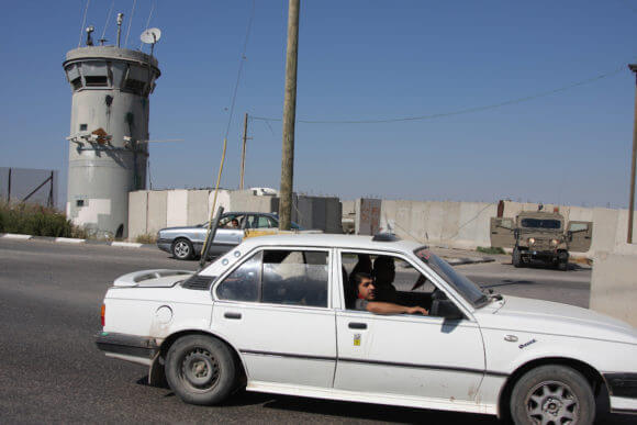A Palestinian car drives by the Atara checkpoint north of the West Bank town of Ramallah, 2009. (Photo: Issam Rimawi/APA Images