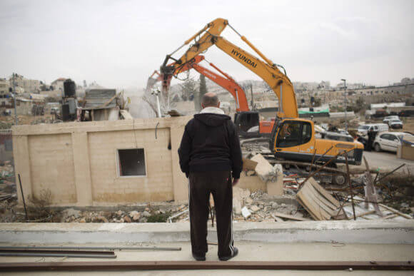 A member of the Adgluni family watching his house being demolished by Israeli authorities in Beit Hanina, East Jerusalem on January 27, 2014. (Photo: Activestills)