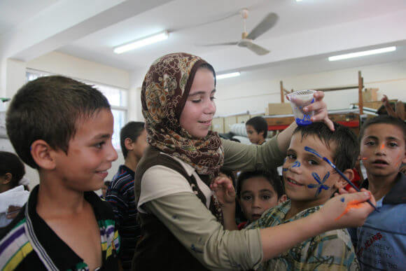 """Palestinian children affected by the war attend a group class as part of the United Nations community mental health programmes in the Gaza Strip on August 2, 2014 at a school converted to a refuge in Jabalia, in the north of the Gaza strip. """"To prevent children from processing and thinking about all these issues we try to distract them, to help them live some joy, to have a little fun inside the shelter"""", said psychiatrist Dr. Iyad Zaqout, who manages the program. (Photo: Ezz al-Zanoun/APA Images)"""