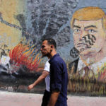 Palestinians walk past a mural depicting U.S. President Donald Trump, in Gaza City, June 24, 2019. (Photo: Ashraf Amra/APA Images)