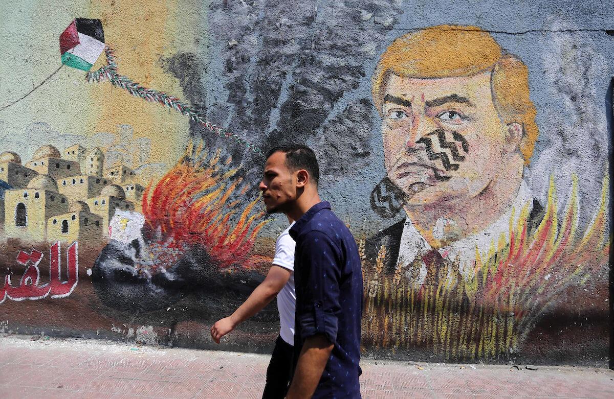 Palestinians walk past a mural depicting U.S. President Donald Trump, in Gaza City, June 24, 2019. (Photo: Ashraf Amra/APA Images)