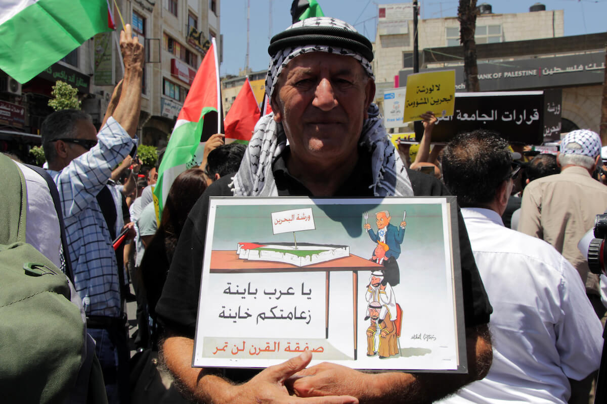 Palestinians hold placards during a protest against the economic workshop in Bahrain, in the West Bank city of Ramallah on June 24, 2019.