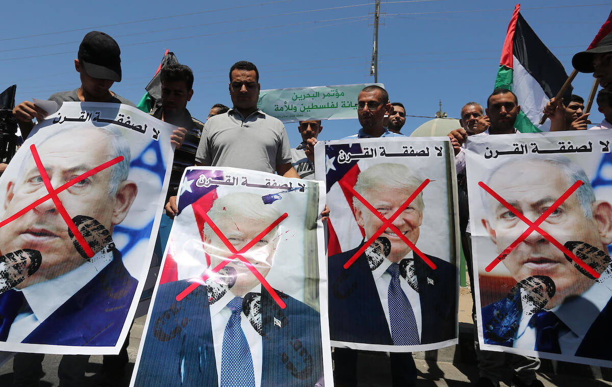 Palestinian protesters hold posters during a protest against the Bahrain economic workshop, in Khan Younis in the southern of Gaza strip, on June 26, 2019. (Photo: Ashraf Amra/APA Images)