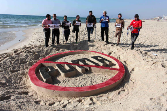 Palestinian amputees who were injured by Israeli forces stand in front a sand castle in a protest calling to boycott sportswear retailer Puma, on the beach of Gaza City on May 29, 2019. Puma is the main sponsor of the Israel Football Association (IFA), which includes teams in Israel'i settlements. (Photo: Mahmoud Ajjour/APA Images)