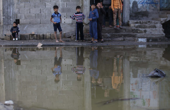 Palestinians look at a flooded street with sewage in al-Sabra neighborhood, in Gaza City on November 13, 2013. The main pump of sewage water which serves thousands of citizens in a densely populated area was stopped during the power cuts in the area due to a fuel shortage, causing sewage overflow out of the station in the lower nearby areas. (Photo: Ashraf Amra/APA Images)