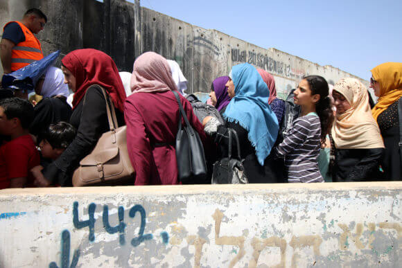 Palestinian women stand in lines at the Qalandiya military checkpoint, May, 2019.