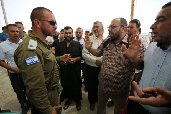 Palestinians argue with an Israeli officer for being prevented from crossing at the Qalandiya military checkpoint, May, 2019.
