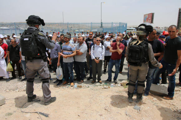Israeli forces surround a group of Palestinians who were turned away from Qalandiya checkpoint after being forbidden from crossing over to Jerusalem, May, 2019.