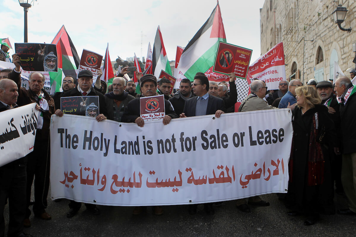 Palestinian protesters hold placards as the convoy of Jerusalem's Greek Orthodox patriarch Theophilos III arrives in the West Bank town of Bethlehem on January 6, 2018 ahead of a Christmas service according to the Eastern Orthodox calendar. The municipalities of Bethlehem, Beit Sahour and Beit Jala, all in the West Bank, called for the boycott over Jerusalem's Greek Orthodox patriarch allegedly allowing controversial real estate sales. (Photo: Wisam Hashlamoun/APA Images)