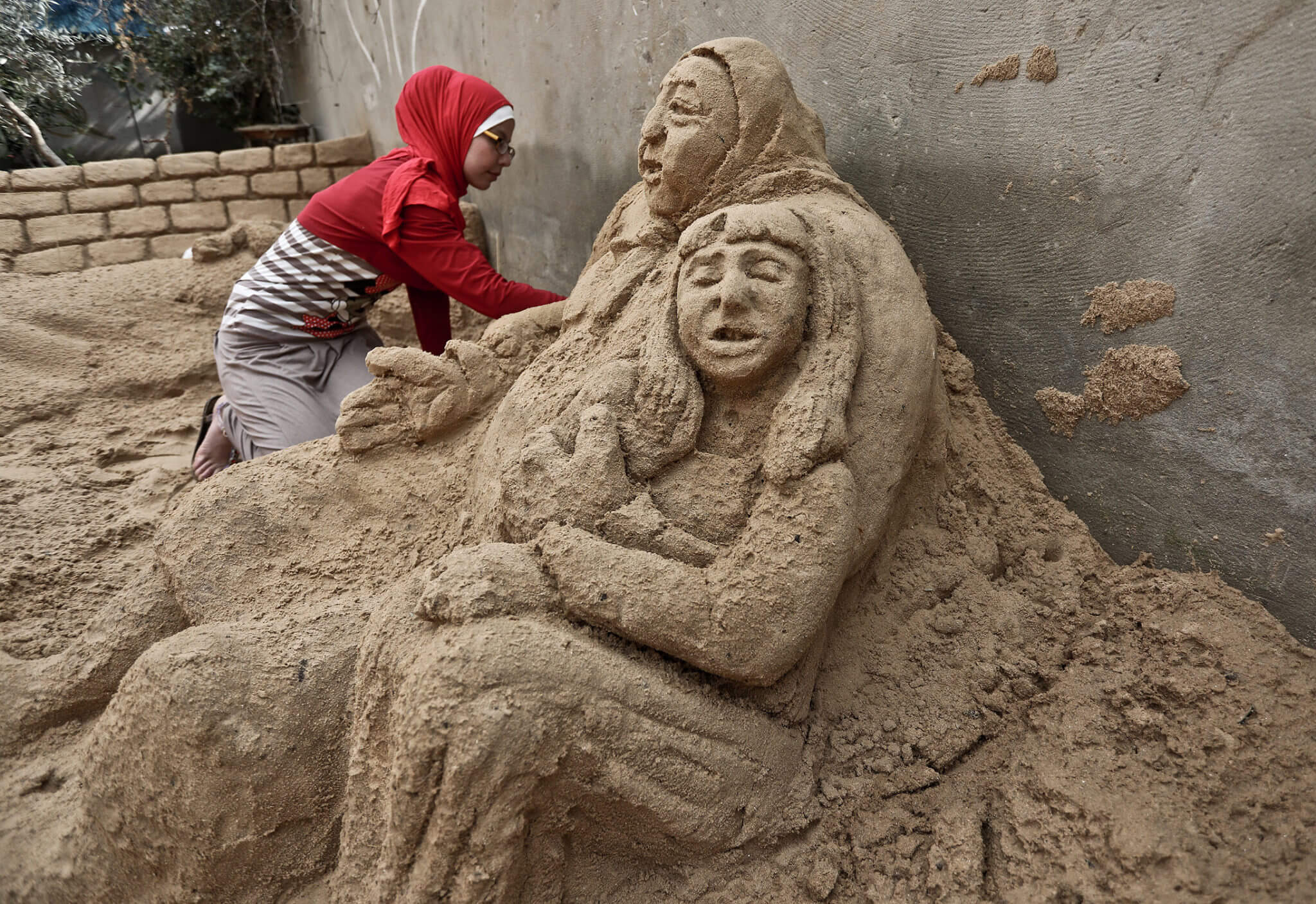 Rana Ramlawi, 20, practices sand sculpture by carving drawings of national symbols on the beach sand near her house